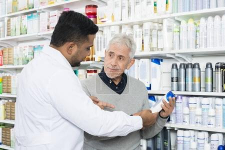 Pharmacist Assisting Senior Customer In Buying Product