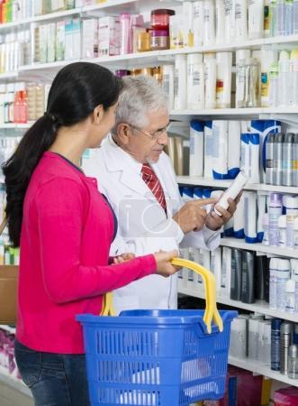 Chemist Assisting Female Customer In Buying Shampoo