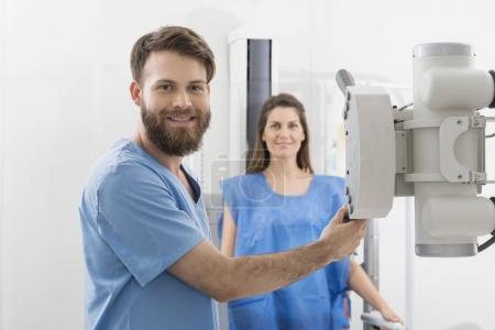 Radiologist Adjusting X-ray Machine Over Female Patient In Hospi