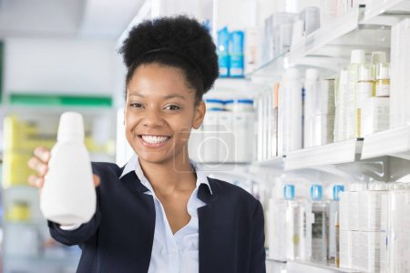 Businesswoman Smiling While Presenting Bottle In Drugstore