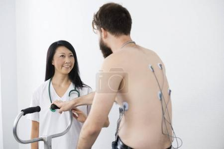 Doctor Looking At Patient Cycling With Electrodes Attached On Ba