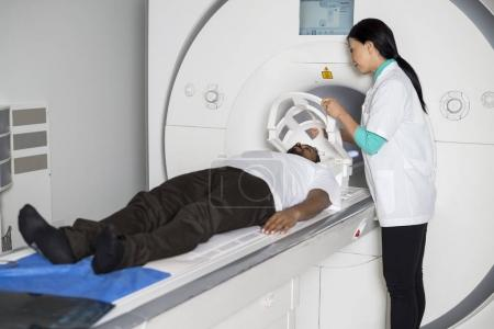 Doctor Fixing Mask To Patient On CT Scan Machine