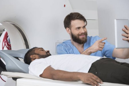 Doctor Showing Digital Tablet To Patient Lying On CT Scanner
