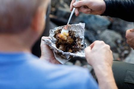 Businessmen Having Food In Foil During Hiking In Forest