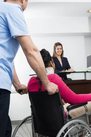 Receptionist Looking At Doctor Pushing Patient On Wheelchair