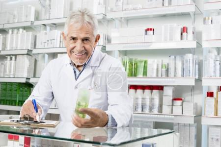 Senior Pharmacist Holding Product While Writing On Clipboard