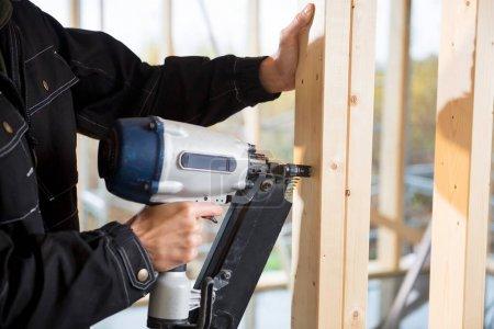 Photo pour Cropped image de jeune charpentier mâle, bois sur le chantier de forage - image libre de droit