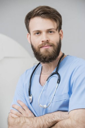 Male Doctor Standing Arms Crossed In Examination Room