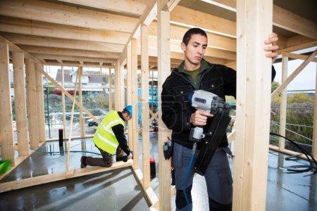 Photo pour Mâle charpentier bois et collègue travaillant sur le chantier de forage - image libre de droit