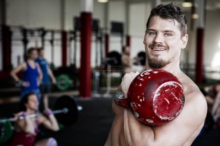 Muscular Trainer Lifting Kettlebell In Gym