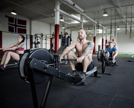 Men And Women Using Rowing Machines In Gym
