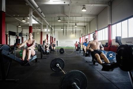 Men And Women Using Rowing Machines