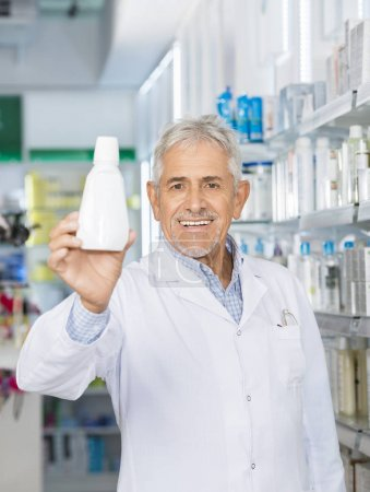 Male Pharmacist Holding Bottle In Pharmacy
