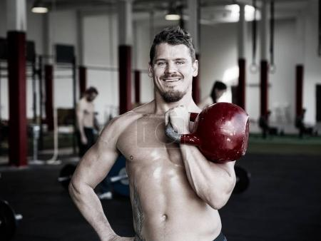 Muscular Trainer Holding Kettlebell In Gym