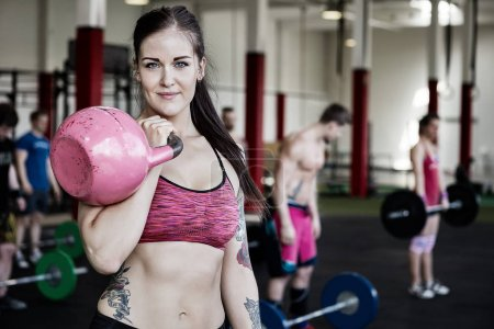 Young Woman Lifting Kettlebell In Gym