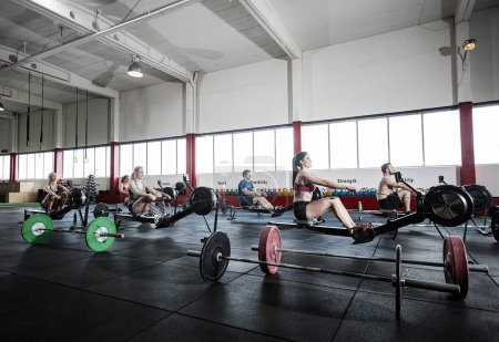 Female And Male Athletes Using Rowing Machine