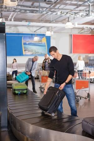Man Collecting Luggage At Conveyor Belt In Airport