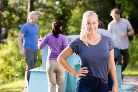 Woman Standing With Hand On Hip While Friends Making Pyramid