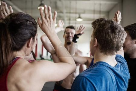 People Giving High Five To Each Other In Gymnasium