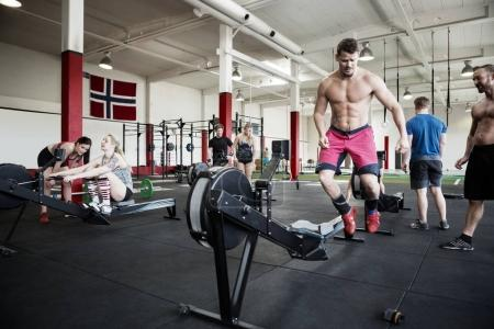 Shirtless Man Jumping By Rowing Machine