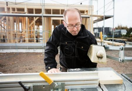 Carpenter Using Table Saw To Cut Plank At Site