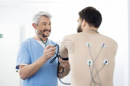 Doctor Examining Patient With Electrodes Attached On Back