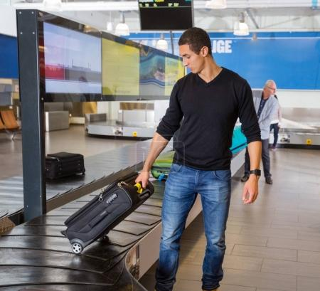 Man Collecting Baggage At Conveyor Belt In Airport