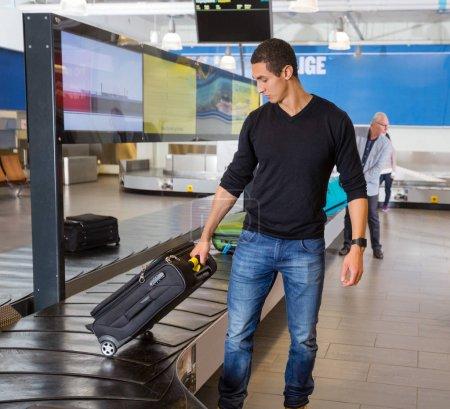 Homme collecte des bagages au tapis roulant à l'aéroport