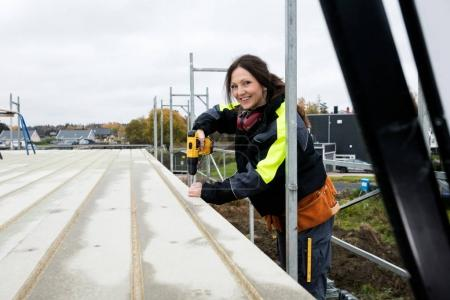 Female Carpenter Drilling Roof At Construction Site