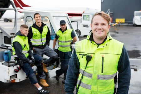 Mid Adult Worker Smiling While Colleagues Resting At Gangway