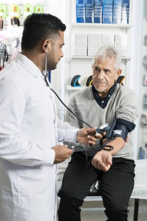 Patient Looking At Chemist Checking Blood Pressure