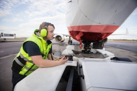 Worker Leaning On Towing Truck With Airplane On Runway