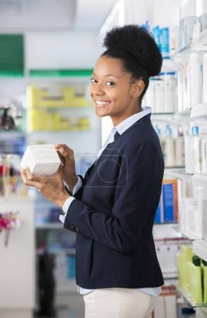 Businesswoman Holding Medicine Box In Pharmacy