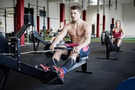 Shirtless Man Using Rowing Machine In Gymnasium