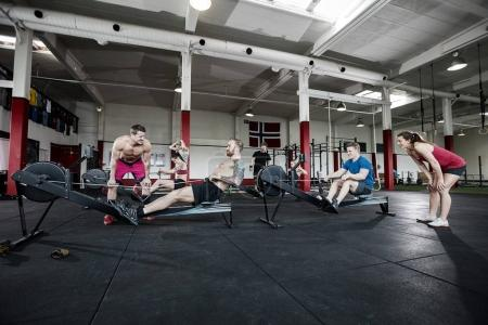 Instructors Motivating Clients Exercising In Gym