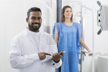 Doctor Using Digital Tablet With Woman Undergoing X-ray Scan