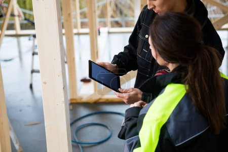 Carpenters Using Digital Tablet In Incomplete Architecture
