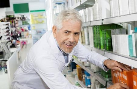 Confident Pharmacist Arranging Medicines On Shelf In Pharmacy