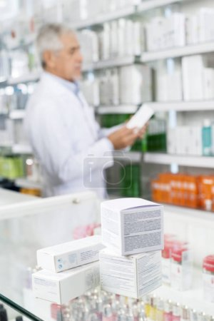 Boxes On Counter With Chemist Working In Pharmacy