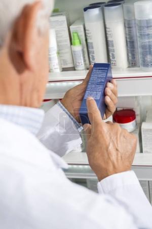 Pharmacist Reading Instructions On Medicine Box In Pharmacy