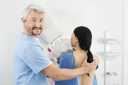 Portrait Of Doctor Assisting Woman Undergoing Mammogram X-ray Te