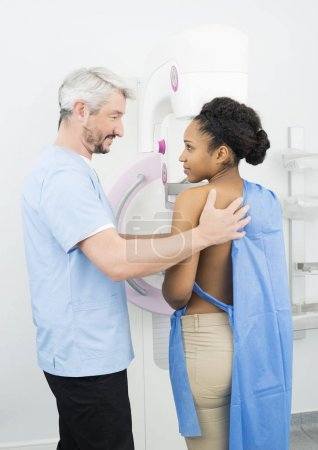 Male Doctor Looking At Patient Undergoing Mammogram X-ray Test