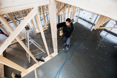 High Angle View Of Carpenter Drilling Wooden Plank