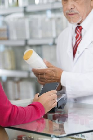 Woman Making NFC Payment While Chemist Holding Shampoo Bottle