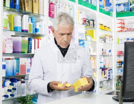 Senior Male Pharmacist Holding Medicines At Counter