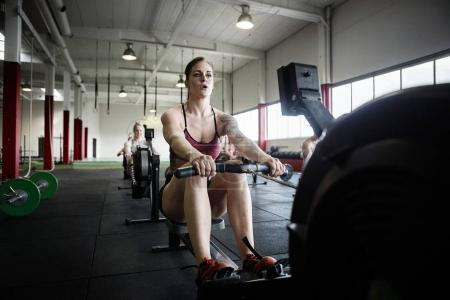 Determined Woman Exercising On Rowing Machine
