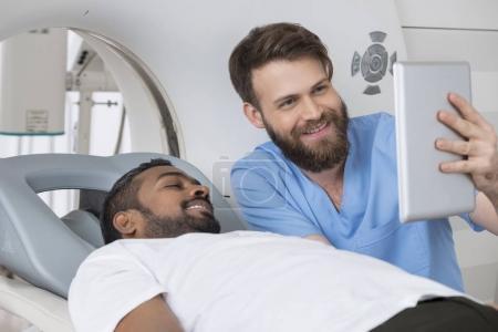 Photo pour Jeune radiologue montrant une tablette numérique à un patient allongé sur un scanner à l'hôpital - image libre de droit