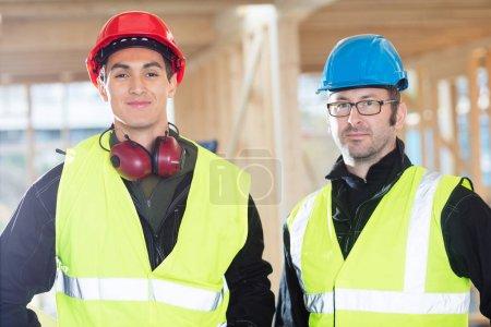 Photo pour Portrait des charpentiers confiants dans des vêtements de protection sur le chantier - image libre de droit