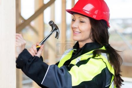 Smiling Female Carpenter Hammering Wood At Site