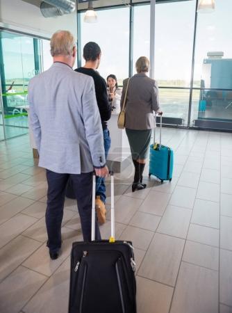 Passagers avec des sacs Trolley en attente à l'accueil à l'aéroport